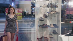 Young joyful woman with shopping bags on the background of shop windows Stock Footage
