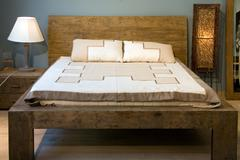 Oold-slyle wooden bed with pillows - stock photo