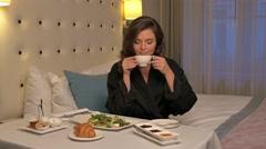 Beautiful woman having breakfast in a hotel room Stock Footage