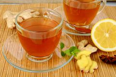 Ginger teas on wooden mat with lemon,anise and mint on mat - stock photo