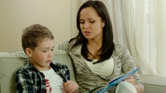 Stock Video Footage of Mother with her son on a sofa in home interior reading book