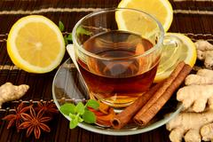 Ginger tea-ingwertee on brown mat with lemon,cinnamon,anise and mint on mat - stock photo