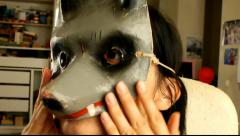 Girl trying on a theatrical rarity mask of the wolf Stock Footage
