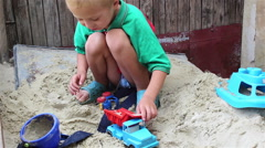 Boy in sand with machine Stock Footage