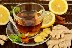Ginger tea-ingwertee on brown mat with lemon,cinnamon and mint on mat - stock photo
