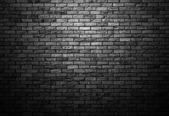 dimly lit old brick gray wall with ligth vignette - stock photo