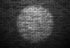 Dimly lit old brick wall enlightened cone of light Stock Photos