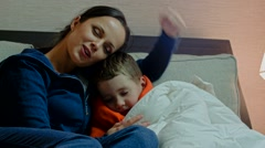 Young mother and her sick son in a bed Stock Footage