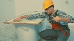 Stock Video Footage of Workman measuring bathtub in new apartment interior