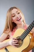 A beautiful young blonde with a classical guitar Stock Photos