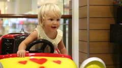Little blonde child rejoice in toy car Stock Footage
