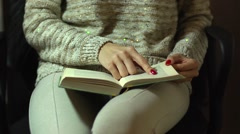 Girl sitting and reading a book with red nail polish fingers over her legs Stock Footage