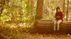 Hipster girl using digital tablet in the forest. Handheld shot Stock Footage