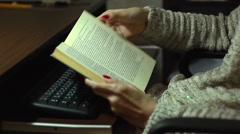 Girl flipping leafing and reading a book over keyboard computer - stock footage