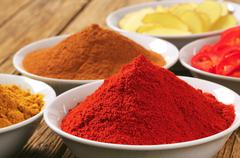 Curry powder, paprika,  ground cinnamon, sliced ginger root and red pepper - stock photo