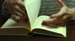 Girl flipping leafing and reading a book with red nail polish fingers - stock footage