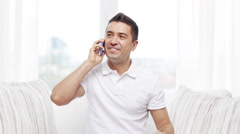 Happy man calling on smartphone at home Stock Footage