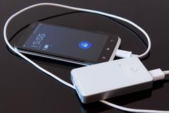 Smartphone charged by power bank - stock photo