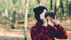 Teenager girl with binoculars in the forest. Handheld shot Stock Footage
