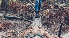 Girl walking on a fallen trunk. Handheld shot Stock Footage