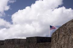 Flag waves over historic military fort. - stock photo