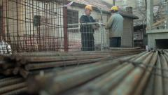 Pile of iron in the foreground, two workers in focus working in the background. Stock Footage