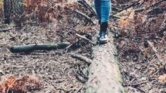 Girl walking on a fallen trunk. Handheld shot - stock footage