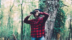 Stock Video Footage of Teenager girl with binoculars in the forest. Handheld shot