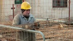 Soiled worker tied rebar with plier and wire. Pile of iron in the background. Stock Footage