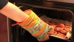 Man with a potholder puts baking chicken in the oven Stock Footage