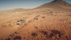 Back aerial view of a 4 by 4 car through the desert. Spain. Stock Footage