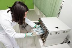 Stock Photo of Dentist Places Medical Autoclave For Sterilising Surgical