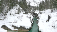 AERIAL: Emerald river running through snowy canyon in winter Stock Footage