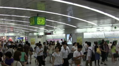 Camera pans across a crowded busy area of Shinjuku station in Tokyo Japan Stock Footage