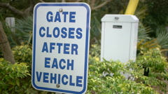 Sign at gated community with gate closing Stock Footage