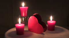 Static shot of burning red candles and candy box for Valentines day with text Stock Footage