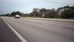 Car driving by on quiet road, Florida. Stock Footage