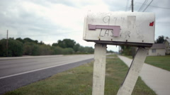 Mailbox by road with cars passing Stock Footage