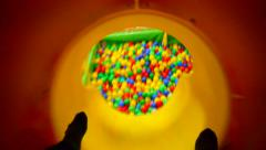 Man coming down the tunnel in the colorful balls Stock Footage