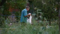 Homeless man looking for food in garbage Stock Footage