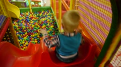 child down with slides, children's city, attraction, boy, colorful slides, happy - stock footage