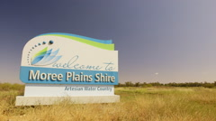 Moree Plains Shire welcome sign on highway, passing vehicles Stock Footage