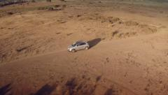 Close up lateral aerial view of a 4 by 4 car through the desert. Spain. Stock Footage