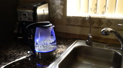 Water boiling in a clear see through LED tea kettle - automatically shuts off Stock Footage
