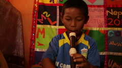 Kathmandu Nepal child plays recorder in music room at childrens home in Eastern Stock Footage