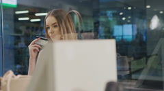 Beautiful girl at the storefront holding credit card and inspect the goods. Shot - stock footage