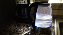 Water boiling in a clear see through LED tea kettle with steam Stock Footage