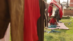 Kathmandu Nepal two children laying on blanket among clothes lines with drying Stock Footage