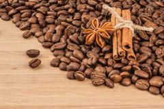 Coffee beans, cinnamon, anise on a wooden table side view. - stock photo
