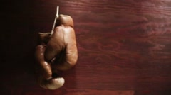 Vintage boxing gloves hanging on wooden background. Stock Footage